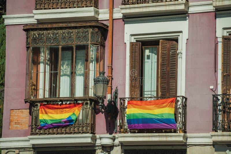 Drapeaux d'arc-en-ciel attachés sur la balustrade dans de vieux balcons de construction à Madrid photo libre de droits