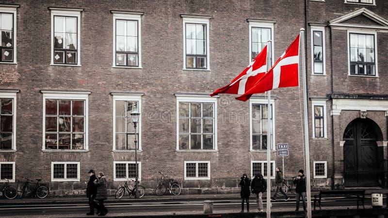 Drapeaux danois à Copenhague Le secteur de Nyhavn est l'un des points de repère les plus célèbres à Copenhague avec les maisons c images libres de droits