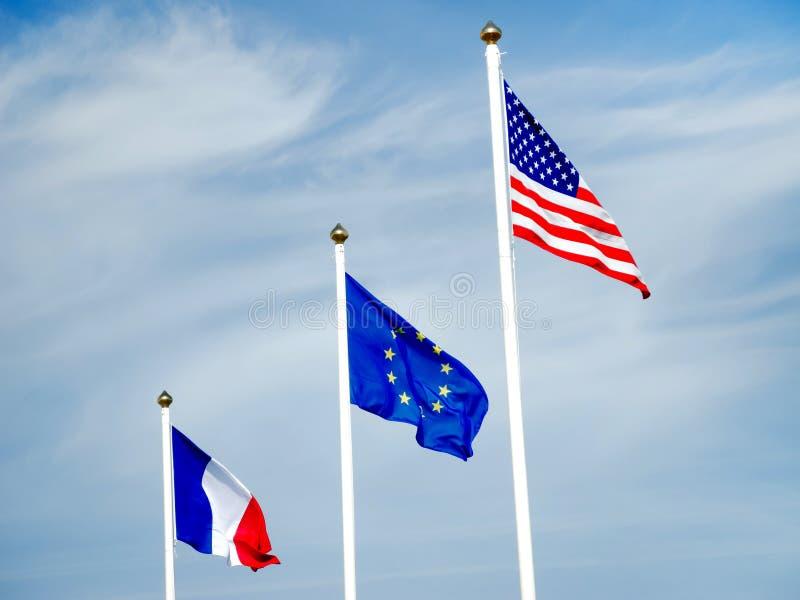 Drapeaux de l'Amérique, de l'union de l'Europe et des Frances sur le mât de drapeau images stock