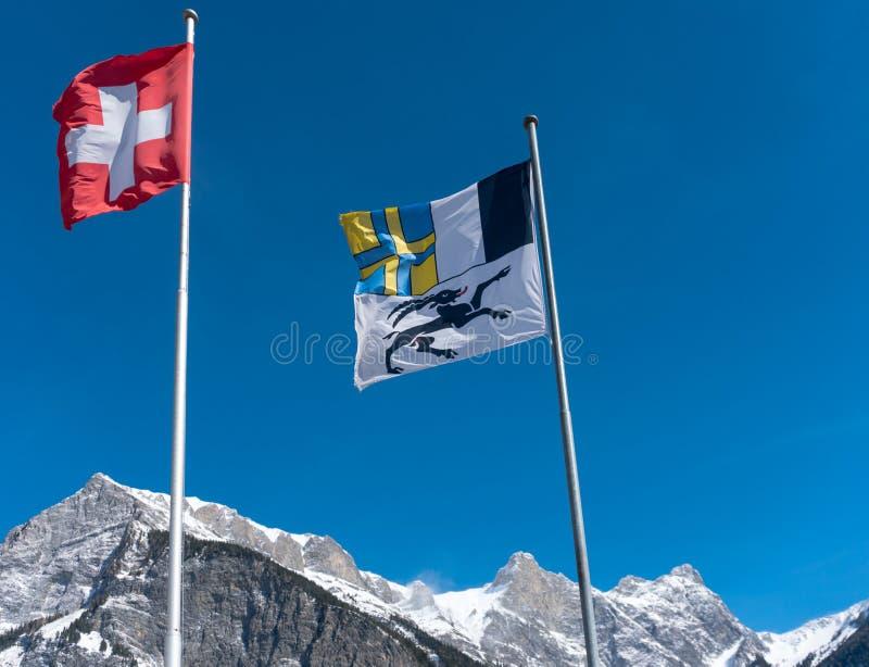 Drapeaux de la Suisse et le canton de Grisons soufflant dans le vent dans un ciel bleu dans les montagnes photographie stock