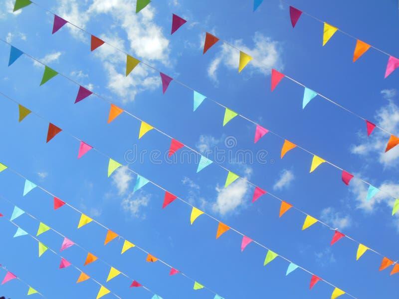 Drapeaux de papier multicolores d'étamine en ciel bleu images stock