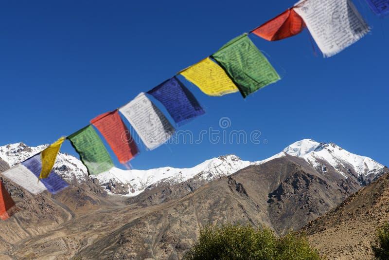 Drapeaux de prière de gamme et de Tibétain de montagne de neige dans le village, route Ladakh, Inde de vallée de Leh-Nubra image libre de droits