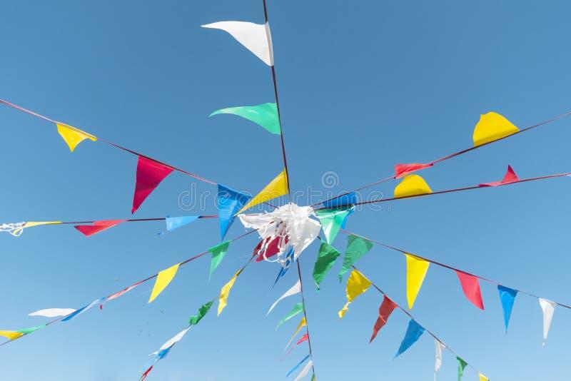 Drapeaux donnants un petit coup de partie sur le ciel bleu d'A photo stock