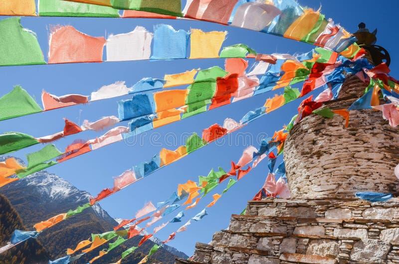 Drapeaux et montagne tibétains colorés de neige à la région scénique Chine de Siguniang image stock