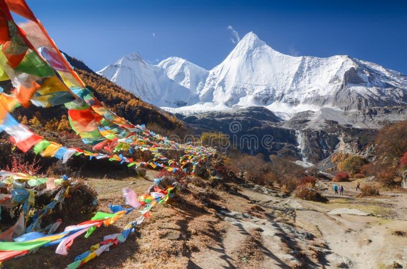 Drapeaux et montagne tibétains colorés de neige à la réserve naturelle de Yading dans la saison d'automne images stock