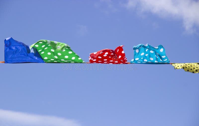 Drapeaux multicolores sur le fond du ciel clair photographie stock libre de droits