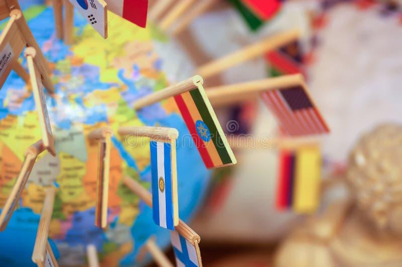 Drapeaux nationaux coincés dans le globe photographie stock libre de droits