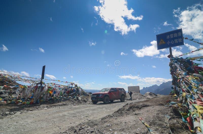 Drapeaux tib?tains color?s avec le ciel bleu au point de vue le long de la route ? la r?serve naturelle de Yading photo stock