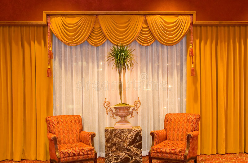 Draped curtains and chairs stock images