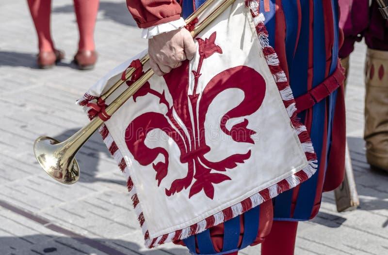 Drapeer met Florentijnse rode lelie en trompet royalty-vrije stock afbeelding