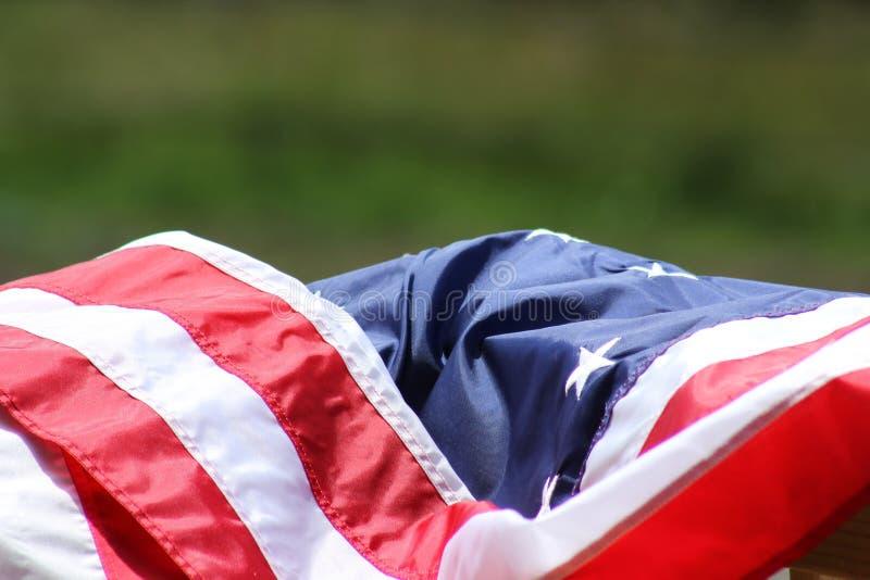 Draperad amerikanska flaggan med gräs- bakgrund royaltyfri fotografi