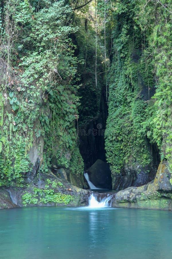 Draperende waterval in smalle en donkere rotsachtige canion Blauwe lagune op het eiland van Bali in Indonesië Natuurlijk meer met royalty-vrije stock foto's