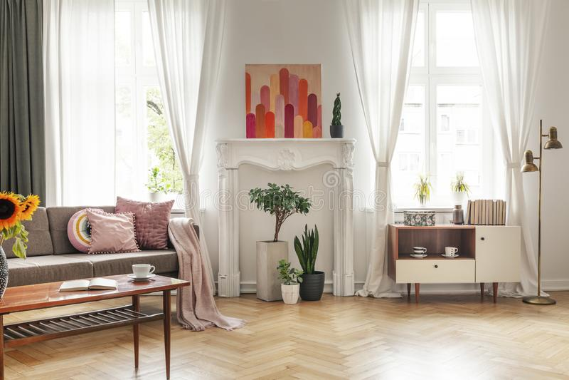 Drapes στα παράθυρα και αφίσα στο άσπρο εσωτερικό καθιστικών με τον καναπέ και το ντουλάπι Πραγματική φωτογραφία στοκ φωτογραφίες με δικαίωμα ελεύθερης χρήσης