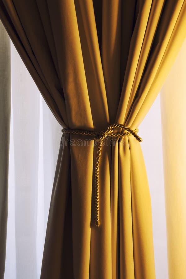 Drapiertes Gewebe des Vorhangs gelbes Fenster stockfoto