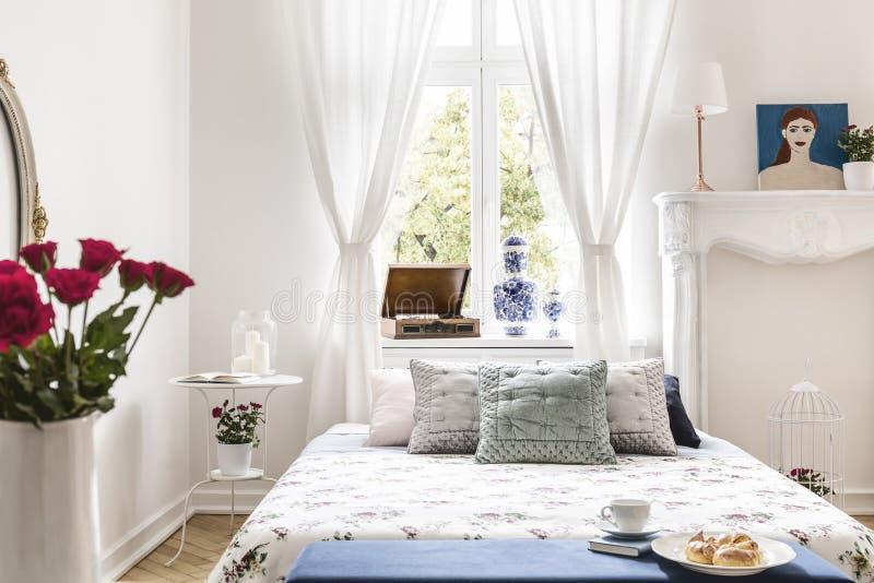 Drapuje przy okno nad łóżko z poduszkami w białym sypialni interi zdjęcie stock