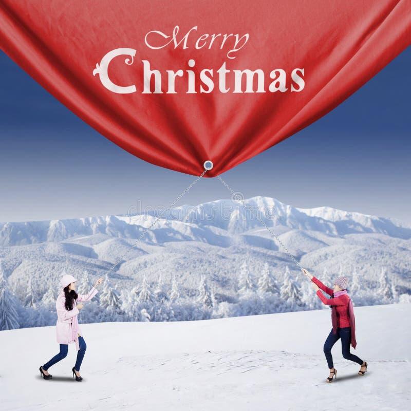 Drar ung kvinna två ett julbaner royaltyfri bild
