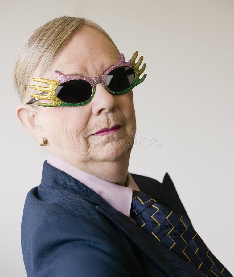 Drastische ältere Frau, die lustige Gläser trägt stockfotos