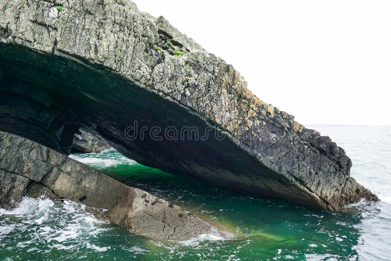 Drastische Gesteinsschichten tauchen von der Klippe in Knickenten- und Aquameereswogen auf Schleifen-Kopf-Halbinsel, Grafschaft C lizenzfreie stockfotos