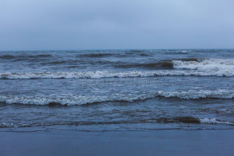 Drastische schäumende spritzende Wellen im Hintergrund des stürmischen Wetters lizenzfreie stockfotos