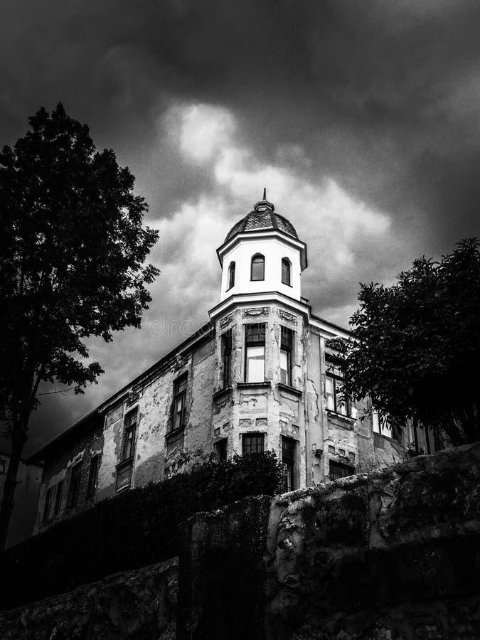 Drastische Szene eines alten Hauses unter bewölktem Himmel stockbild