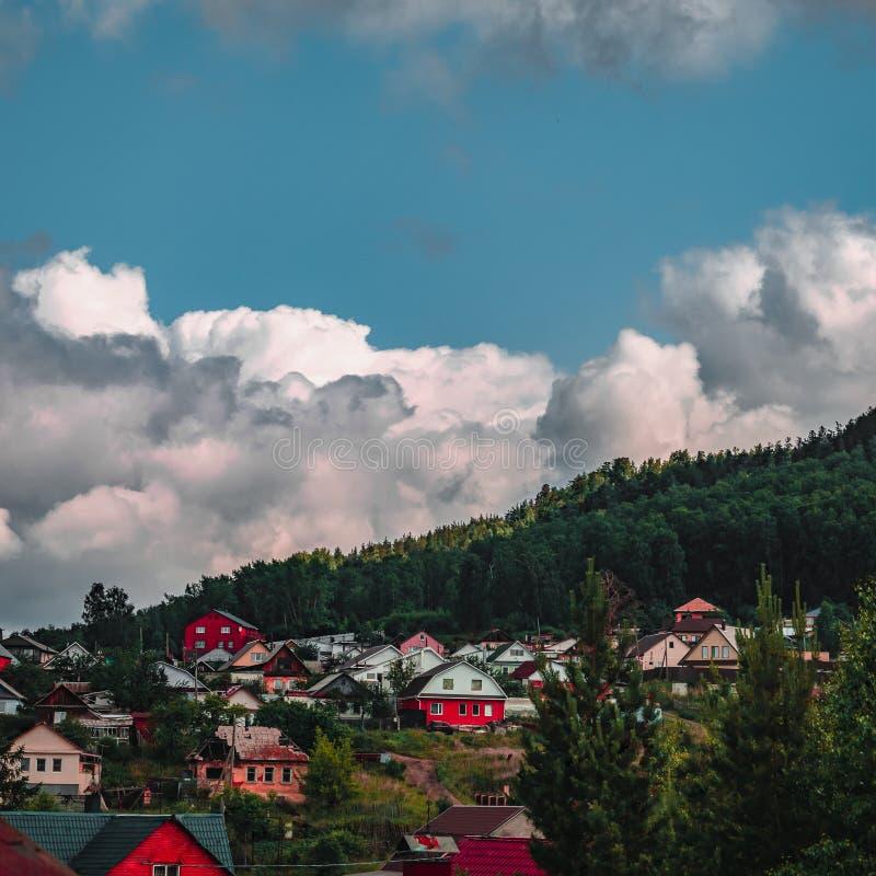 Drastische szenische Ansicht des Bergdorfes mit Wolken über dem Wald stockbilder