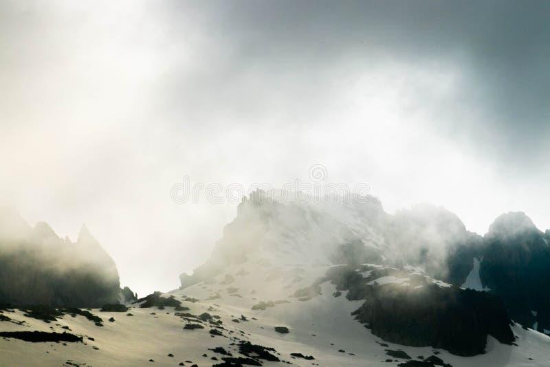 Drastische Wolken auf schneebedeckten Berg stockfotografie