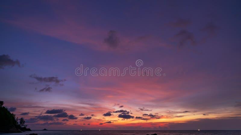 Drastische Wolken, die bunten majestätischen Himmel über Meer überraschen, wenn Zeit, dunkelblauer Stunden-Schattenbildberg geglä lizenzfreie stockbilder