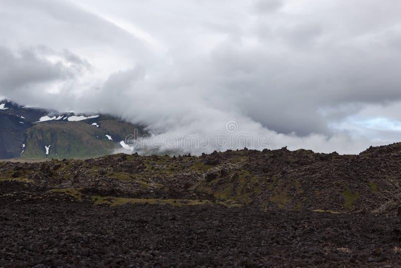 Drastische Wolken, die schneebedeckten Berg Islands bedecken lizenzfreie stockfotos