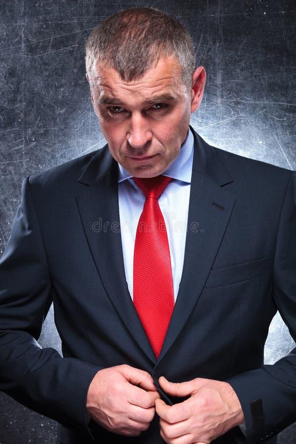 Drastischer ernster reifer Geschäftsmann, der seinen Mantel aufknöpft lizenzfreie stockfotos