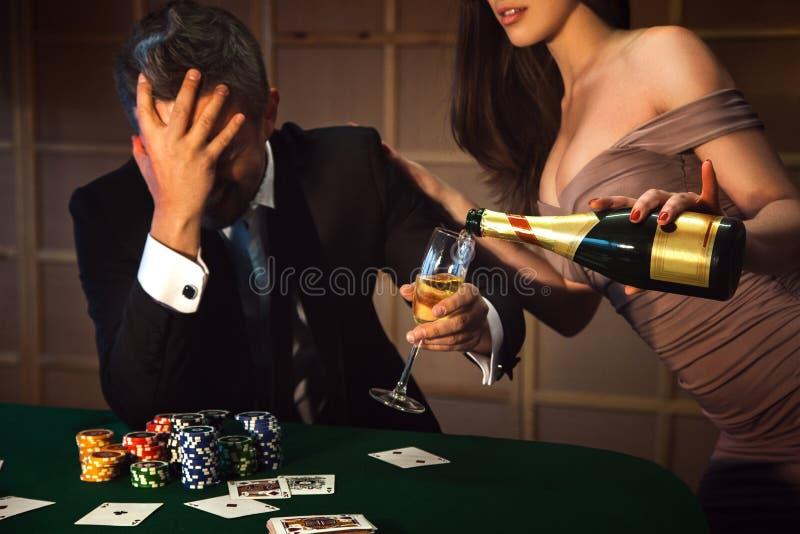 Drastischer Fotoverliererpokermann und -dame gießt ihn ein Glas cha stockfoto