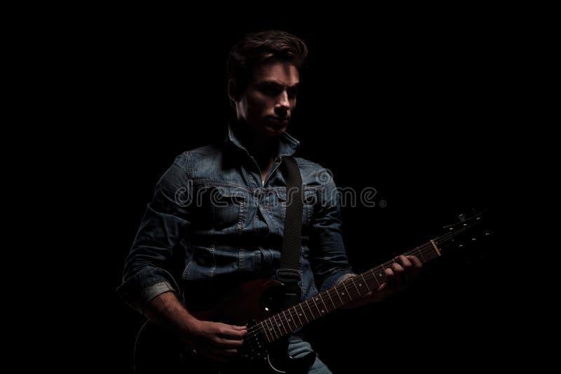 Drastischer Gitarrist, der auf seiner E-Gitarre spielt lizenzfreie stockbilder