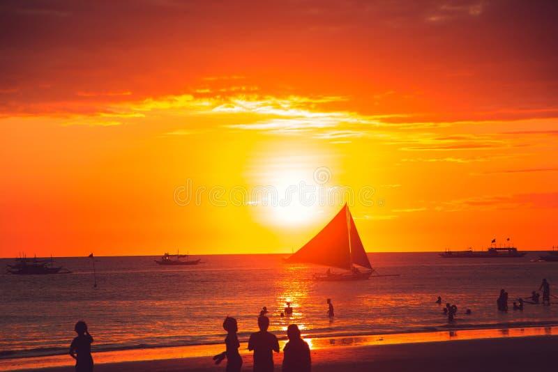 Drastischer goldener Seesonnenuntergang mit Segelboot Junge Erwachsene Reise zu Philippinen Tropische Luxusferien Boracay-Paradie lizenzfreie stockfotografie