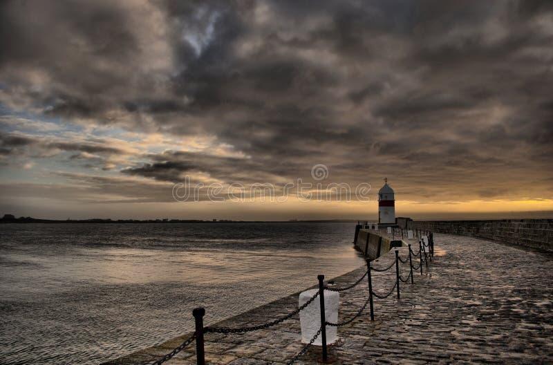 Drastischer Himmel mit Pfad zum Leuchtturm lizenzfreie stockfotos