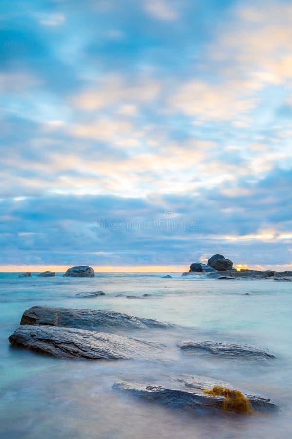 Drastischer Meerblick bei Sonnenuntergang mit silbernen Felsen stockfotos