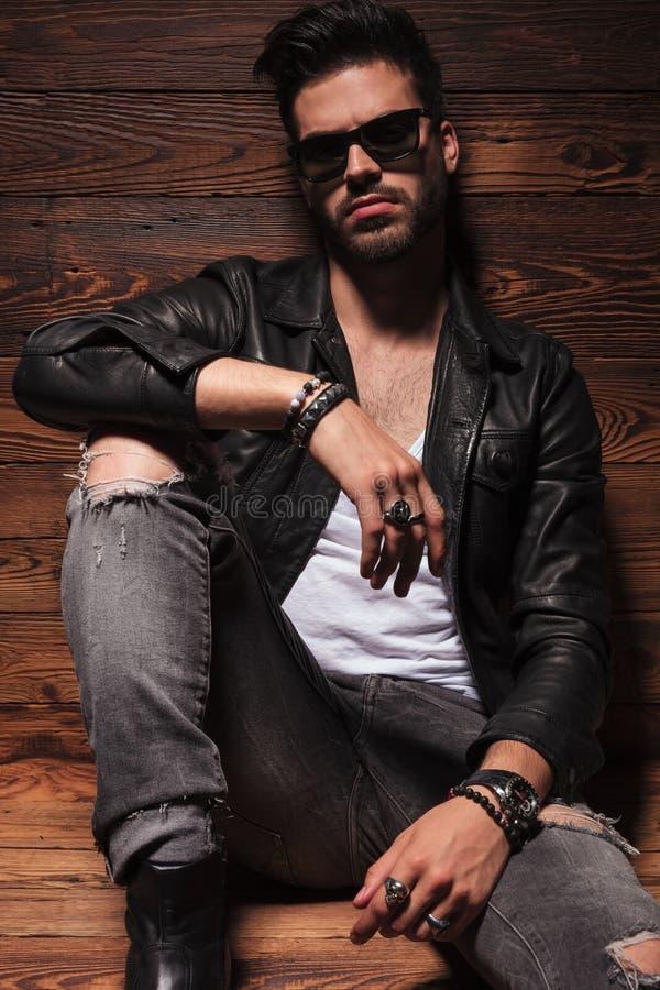 Drastischer Modemann beim Lederjacke- und Sonnenbrillesitzen stockfotografie