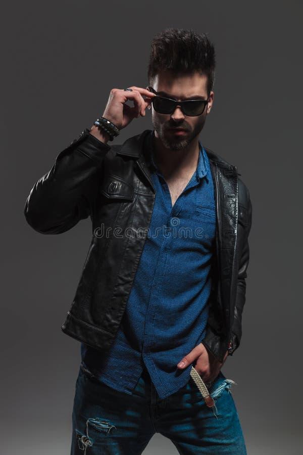 Drastischer Modemann in der Lederjacke seine Sonnenbrille entfernend lizenzfreie stockbilder