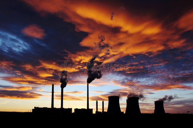 Drastischer orange Sonnenuntergang über Kohleenergieanlage stockfotos