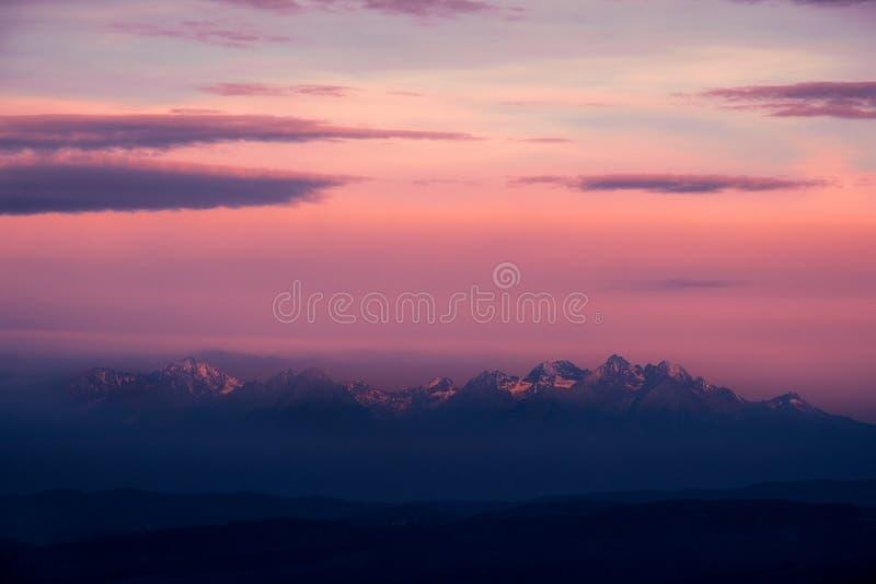 Drastischer Sonnenaufgang mit dunklem schwermütigem Gebirgszug, hohes Tatras, Slowakei stockbild