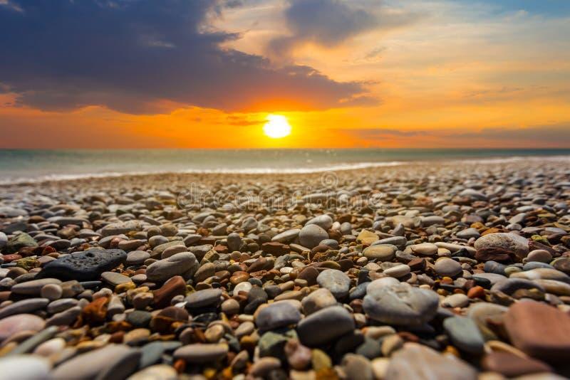 Drastischer Sonnenuntergang über der steinigen Seeküste lizenzfreie stockfotos