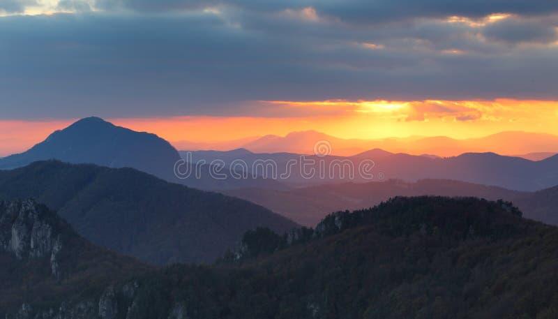 Drastischer Sonnenuntergang strahlt hinter Schattenbild des Berges aus lizenzfreie stockbilder