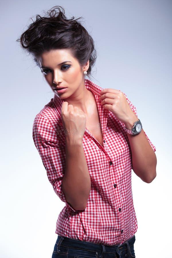 Drastisches Bild einer jungen Frau der Mode, die ihren Kragen zieht stockfoto