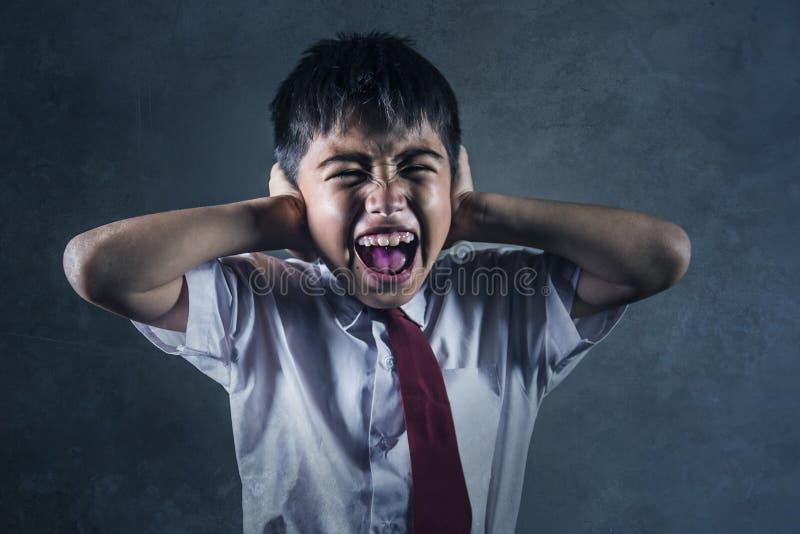 Drastisches Porträt des jungen hoffnungslosen und missbrauchten Schülers in schreiendem alleinopfer der Uniform in der Schule von stockbilder