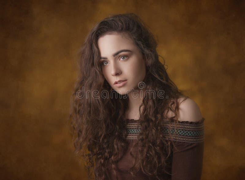 Drastisches Porträt eines jungen schönen Brunettemädchens mit dem langen gelockten Haar im Studio lizenzfreies stockfoto