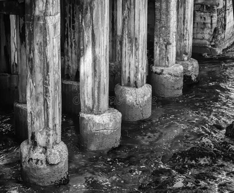 Drastisches Schwarzweiss-Bild, das Pier Piling im Ozean altert stockbilder
