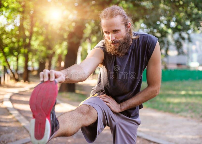 Draußen ausbilden Junger Mann, der seine Beine ausdehnt lizenzfreie stockfotos