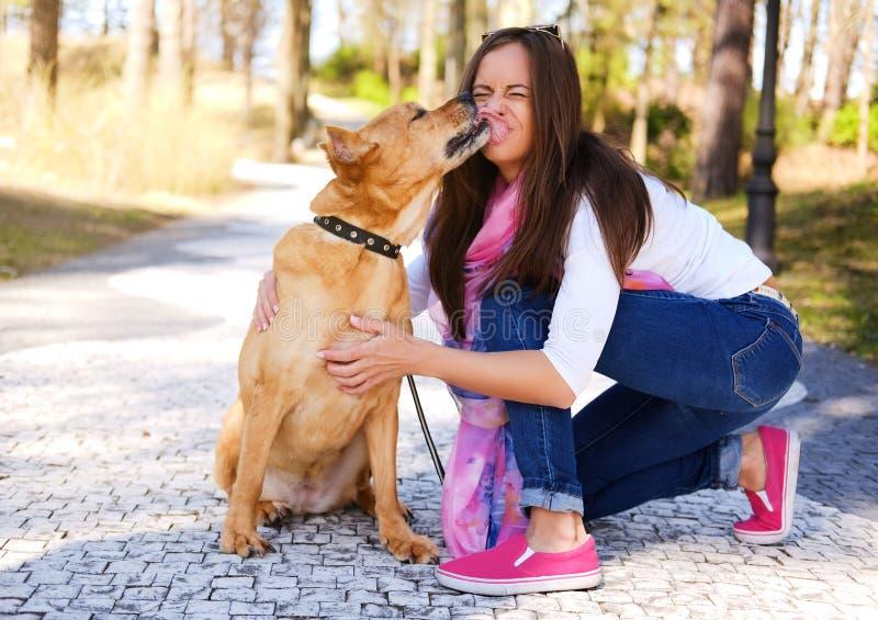 Draußen Lebensstilporträt des schönen Mädchens mit einem netten Hund an stockfoto