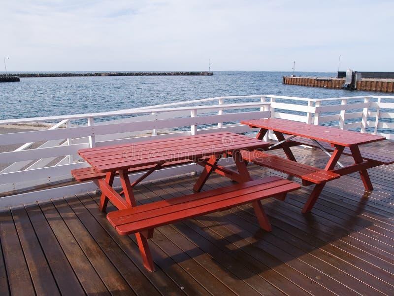 Draußen Picknicktabellen durch das Meer lizenzfreies stockfoto
