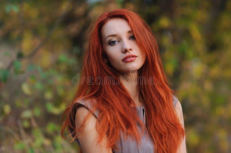 Draußen Porträt der schönen jungen Frau mit dem roten Haar stockbild
