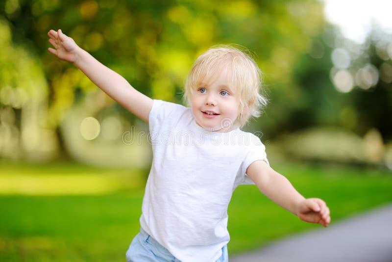 Draußen Porträt des lustigen emotionalen kleinen Jungen, der heraus Zunge haftet lizenzfreie stockbilder