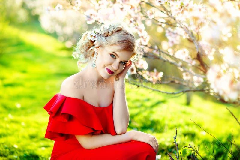 Draußen Porträt des schönen jungen Mädchens im roten Luxuskleid, das im Sommergarten aufwirft stockbild